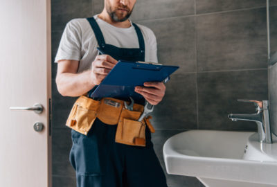 partial view of male plumber with toolbelt writing in clipboard near broken sink in bathroom